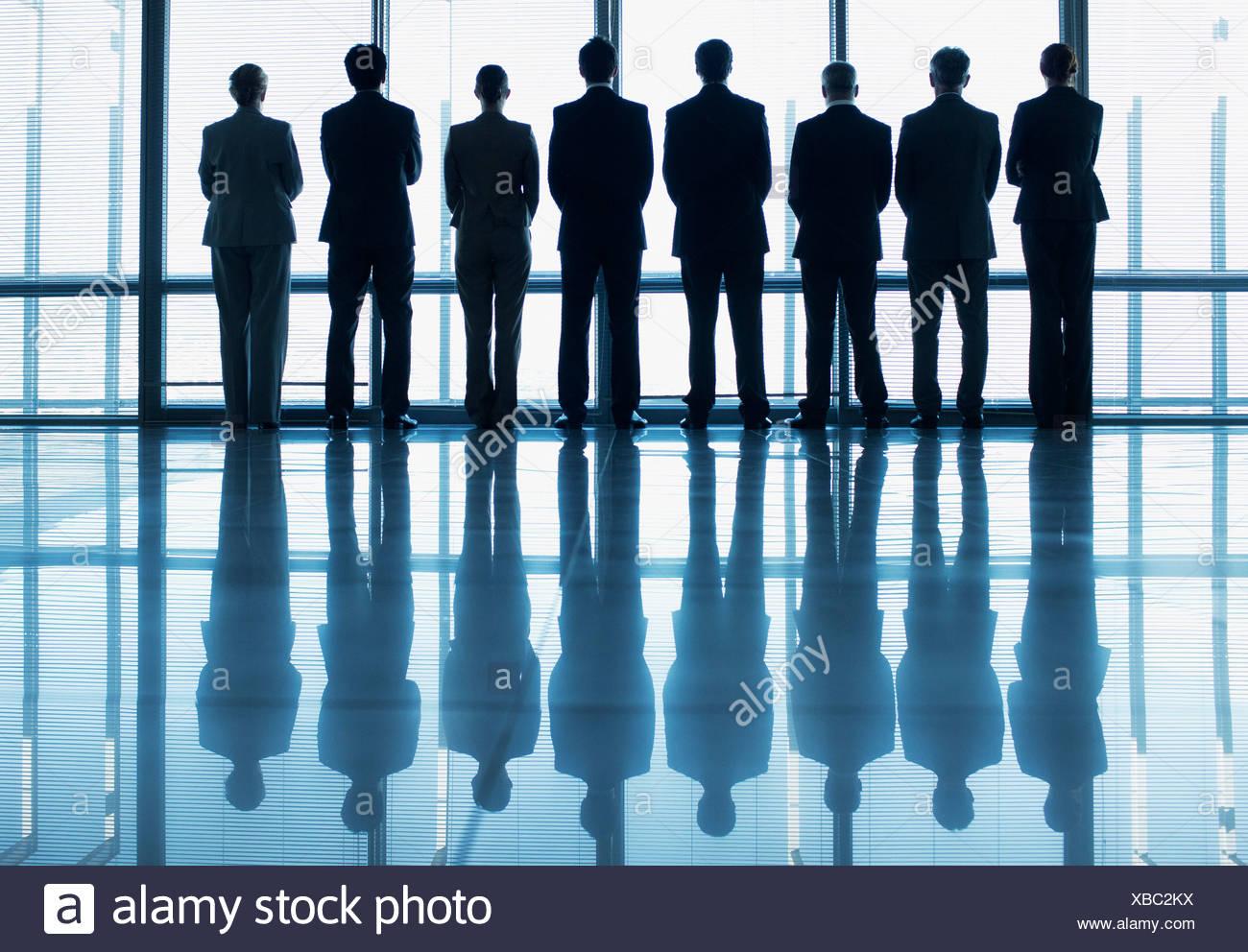 Silhouette de gens d'affaires de suite à la fenêtre du hall des Photo Stock