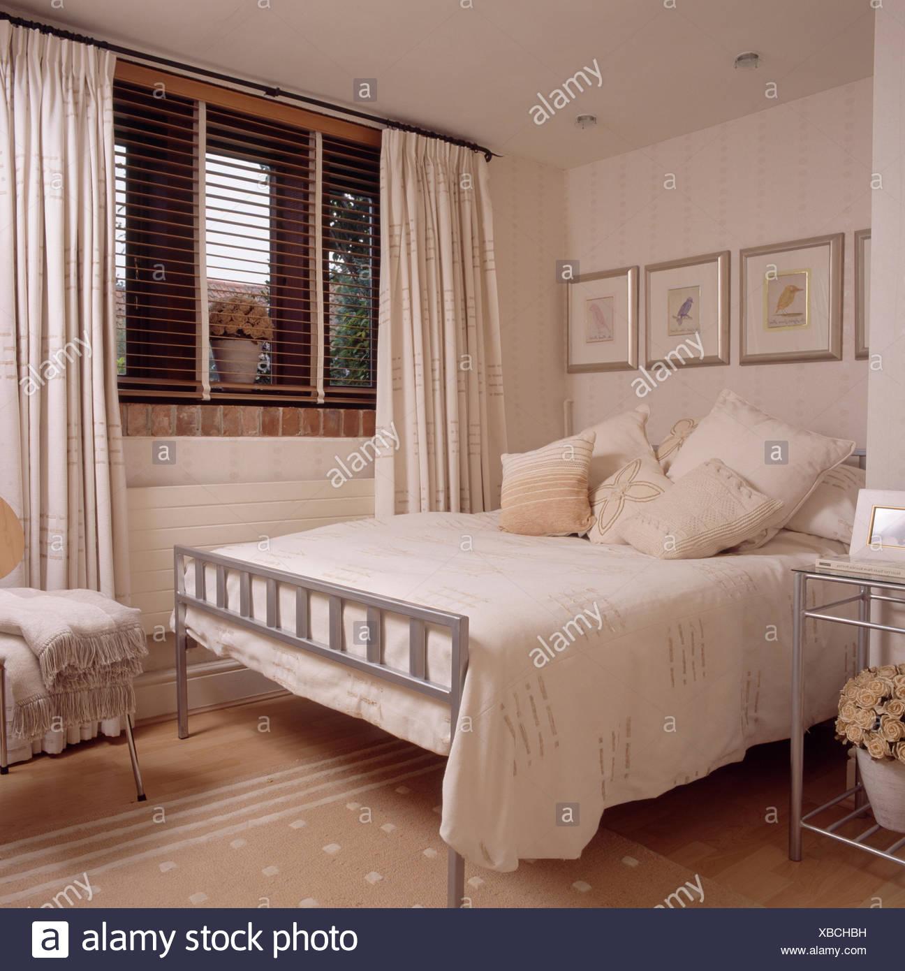 Coussins crème et couvercle sur métal simple lit dans chambre à ...