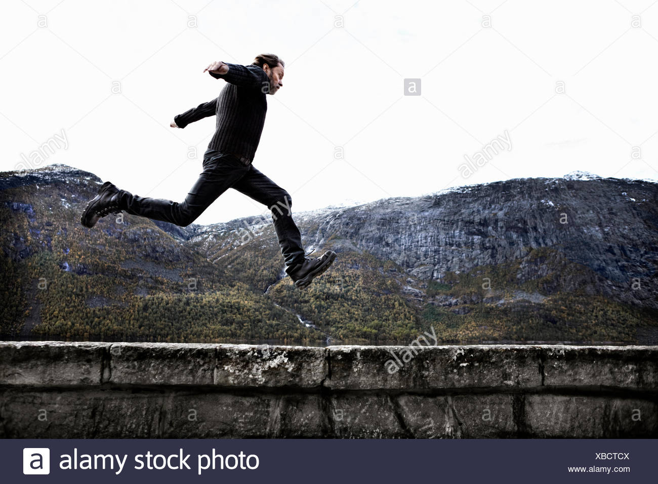 La Norvège, Odda, Man jumping over mur de pierre Photo Stock