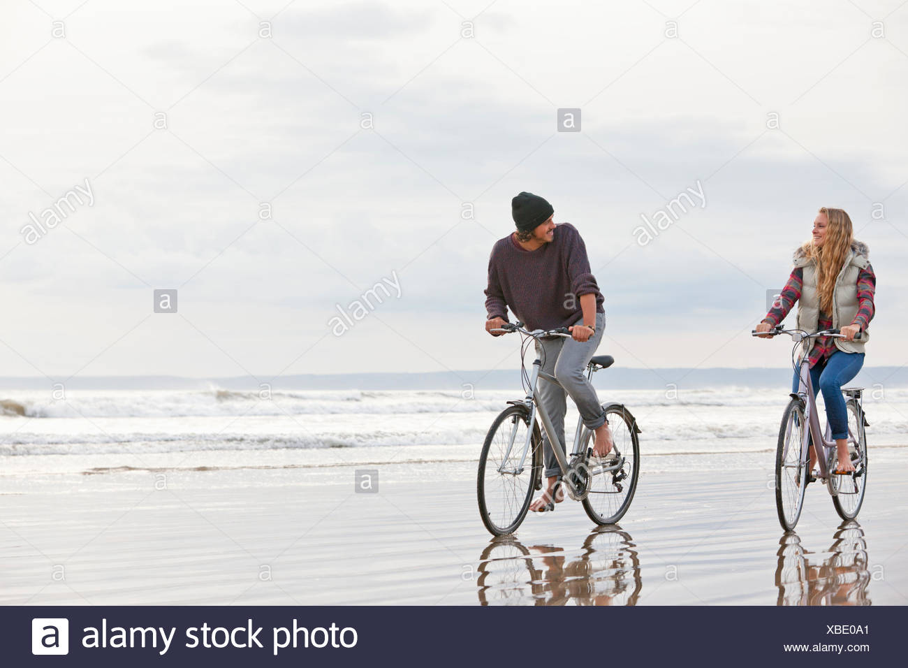 Couple riding bicycles on beach Photo Stock