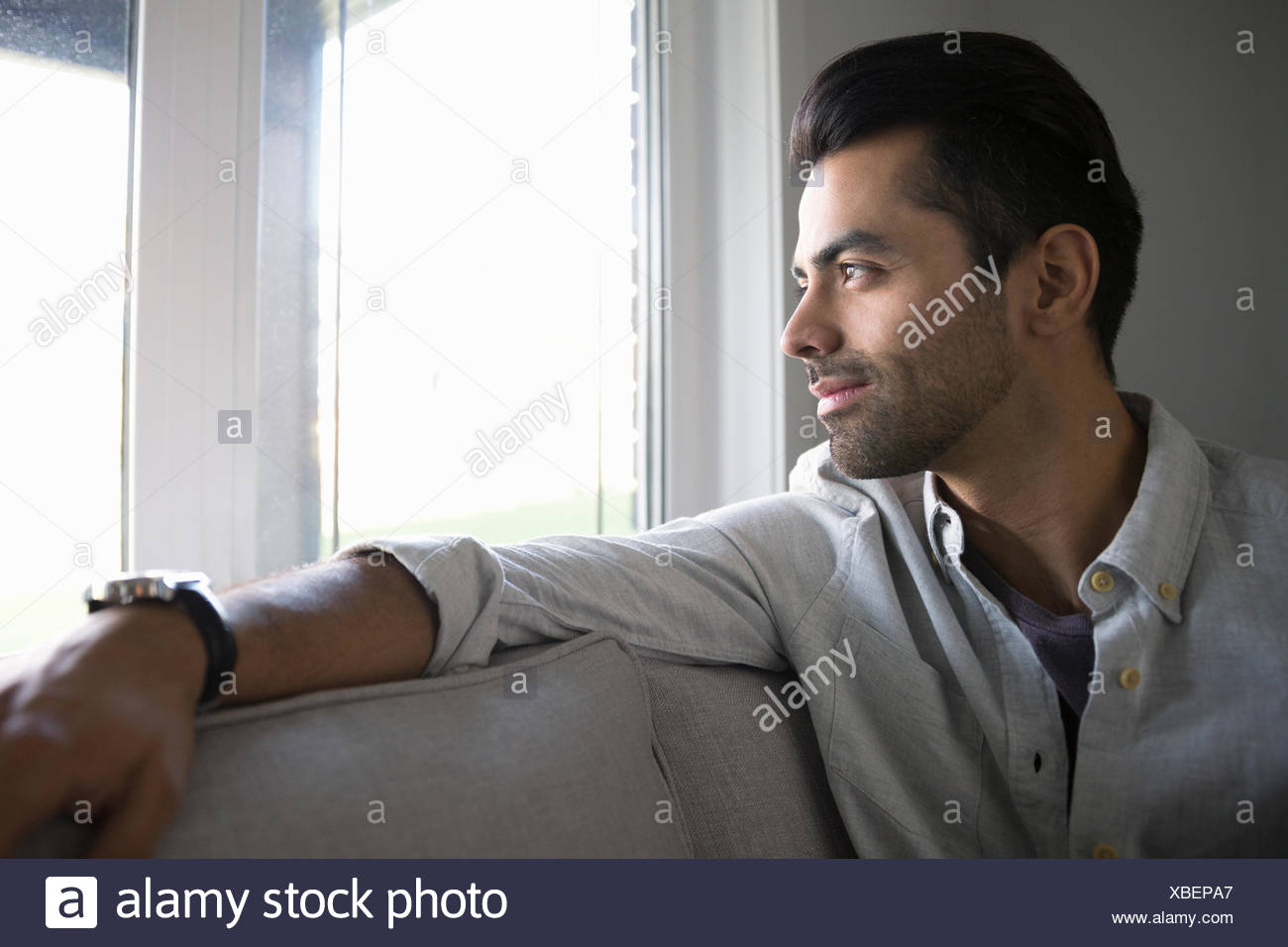 Pensive man on sofa looking out window Photo Stock