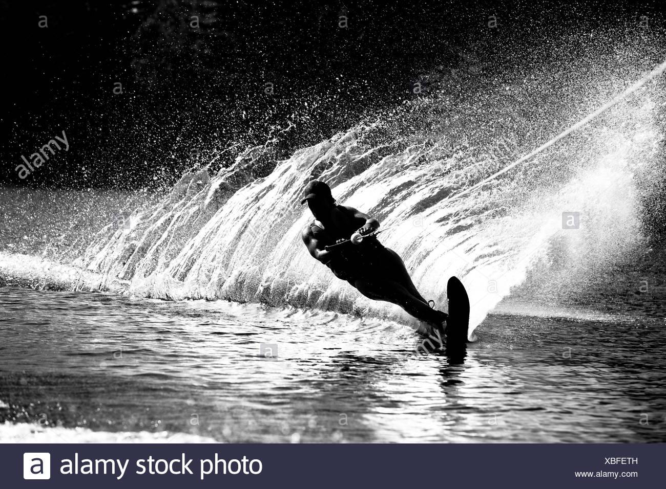 Une skieuse nautique déchire tour provoquant un énorme jet d'eau tandis que le ski sur le lac Cobbosseecontee près de Monmouth, Maine. Photo Stock