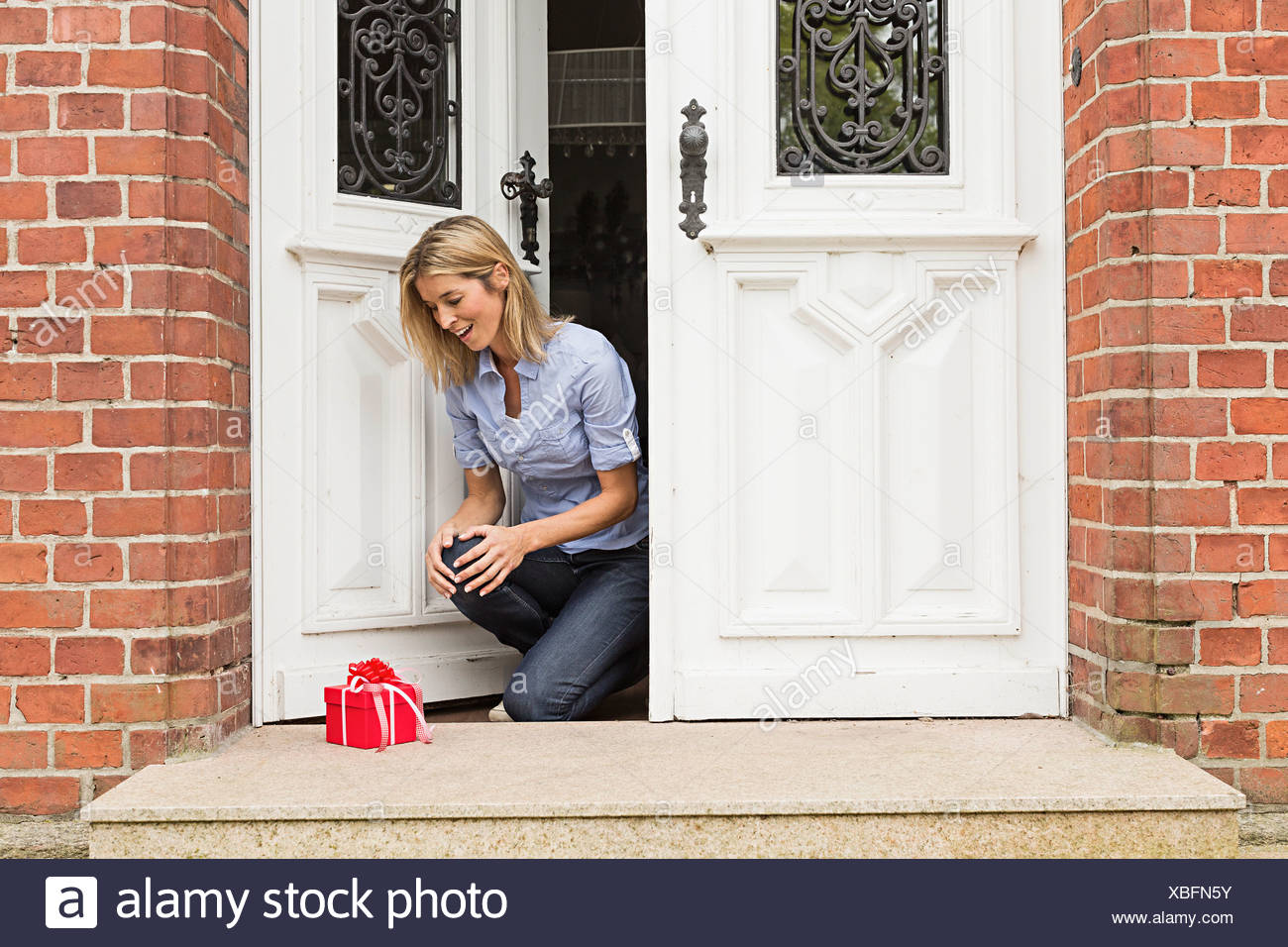Mid adult woman with gift sur porte Photo Stock