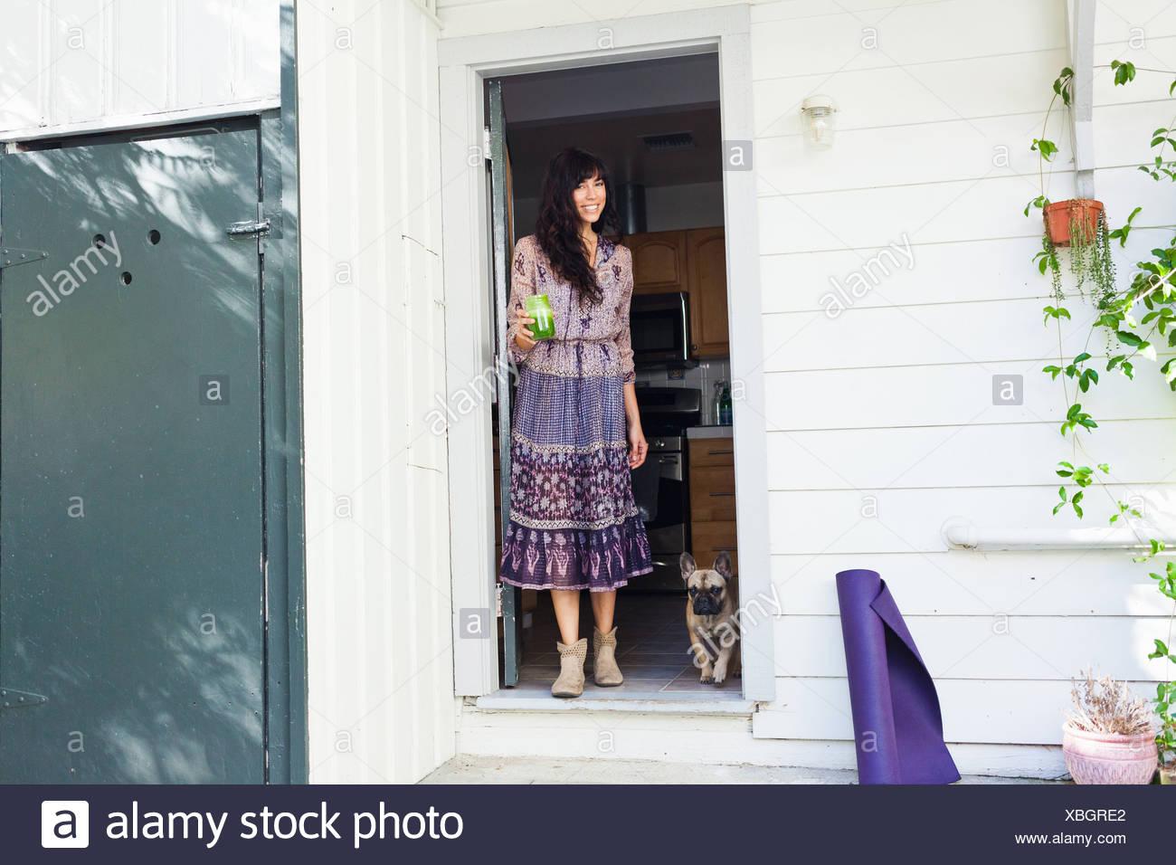 Jeune femme en porte avec du jus de légumes Photo Stock