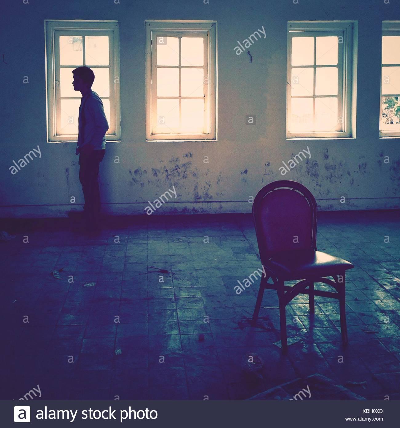 Vue latérale d'un homme debout, dans une salle vide Photo Stock