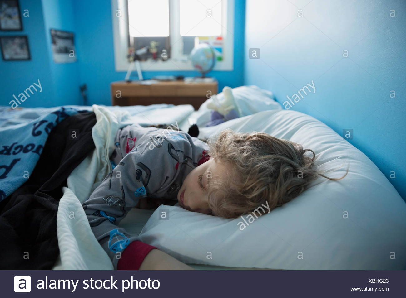 Boy sleeping in bed Photo Stock