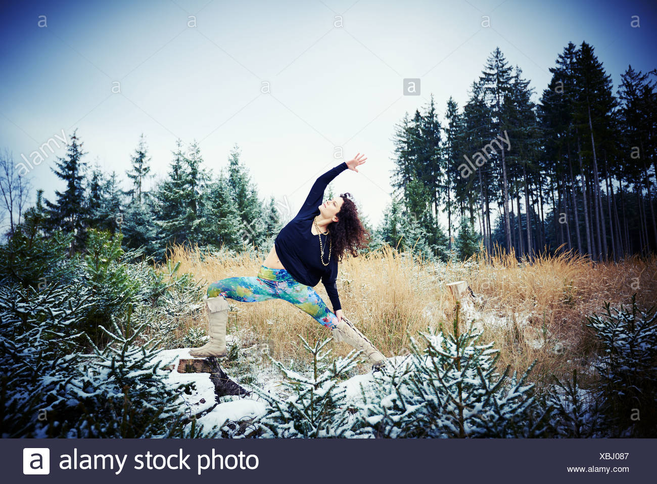 Mid adult woman practicing yoga in forest Photo Stock
