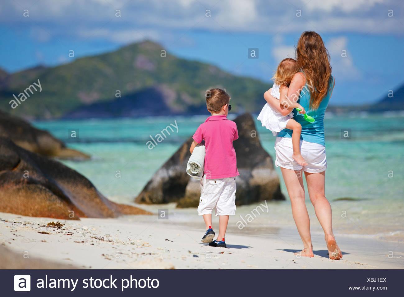 La marche d'une jeune mère avec ses deux petits enfants sur la plage de sable Banque D'Images