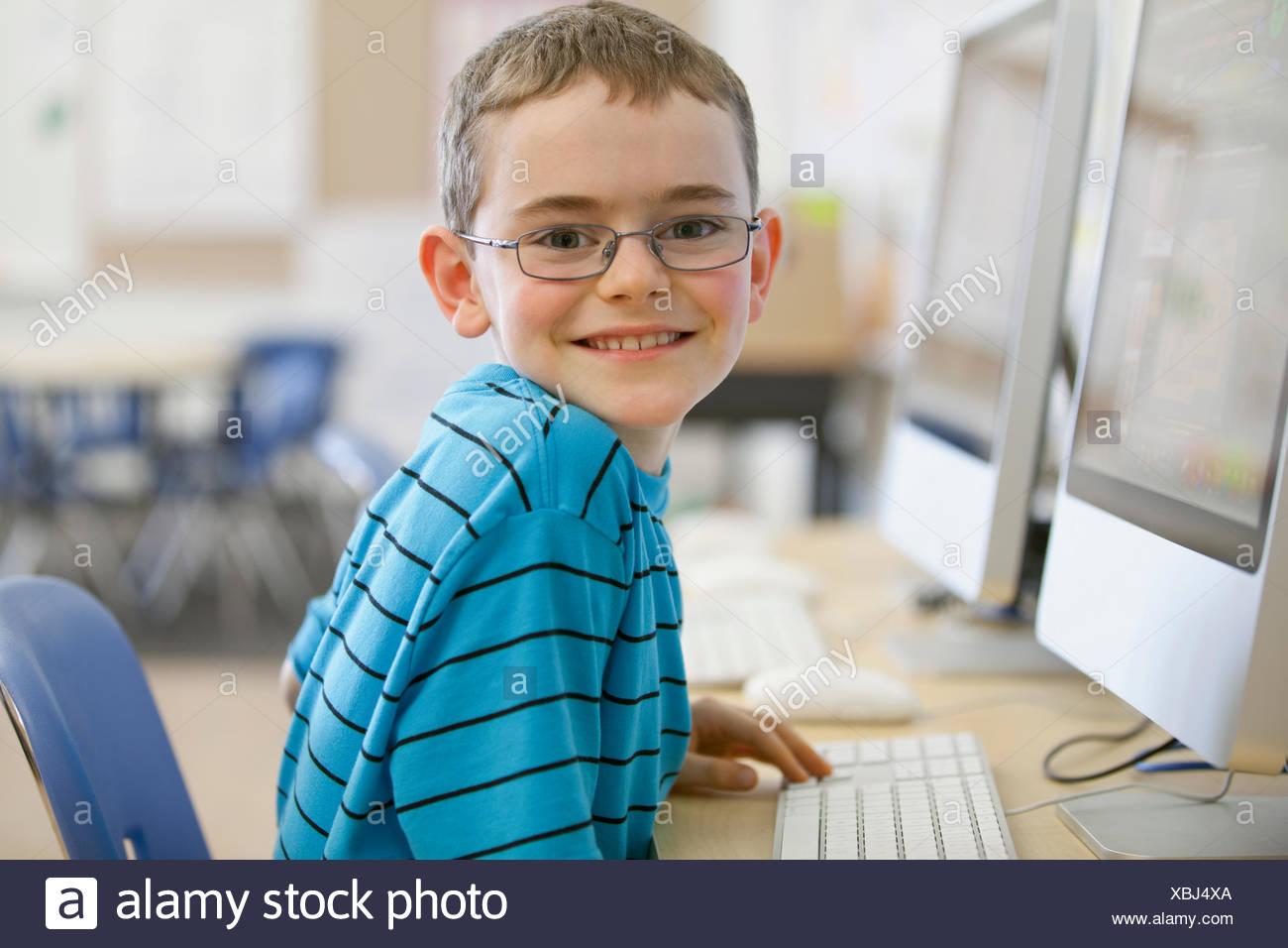 Homme, élève d'école élémentaire sur un clavier d'ordinateur de bureau. Photo Stock