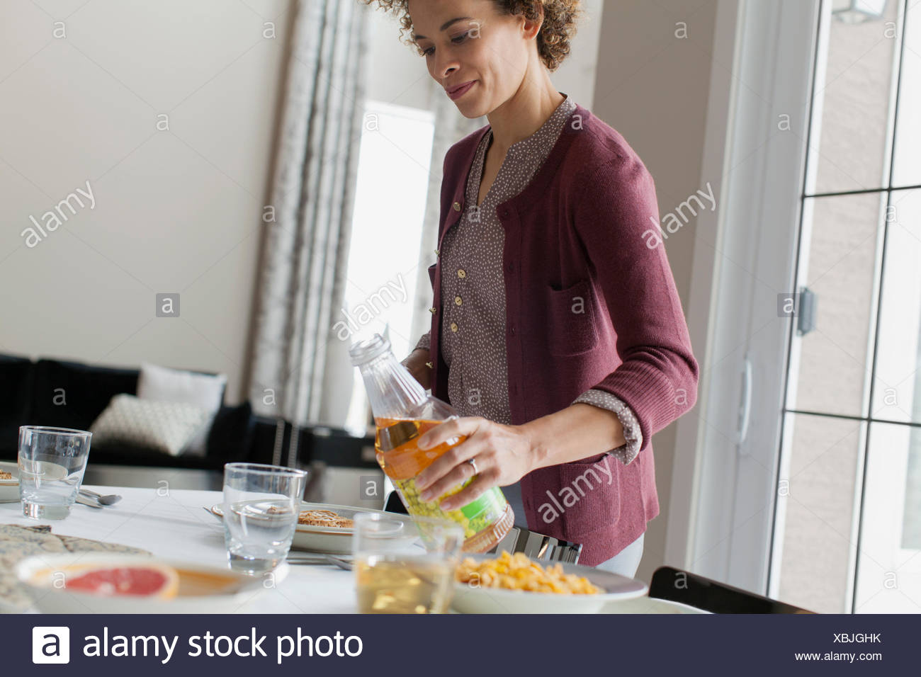 Woman pouring juice à table de petit déjeuner. Photo Stock