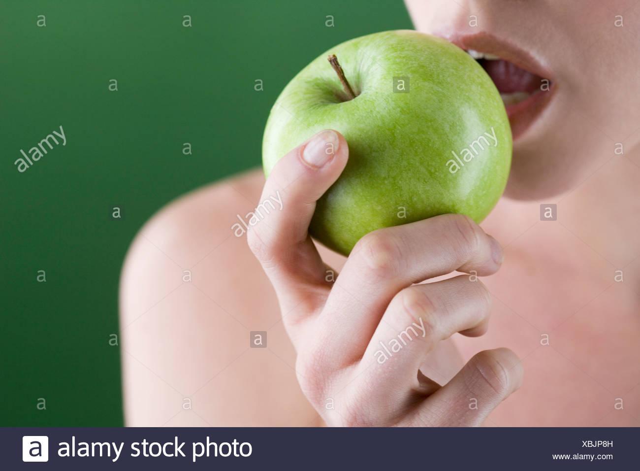 Une jeune femme de manger une pomme, close-up Photo Stock