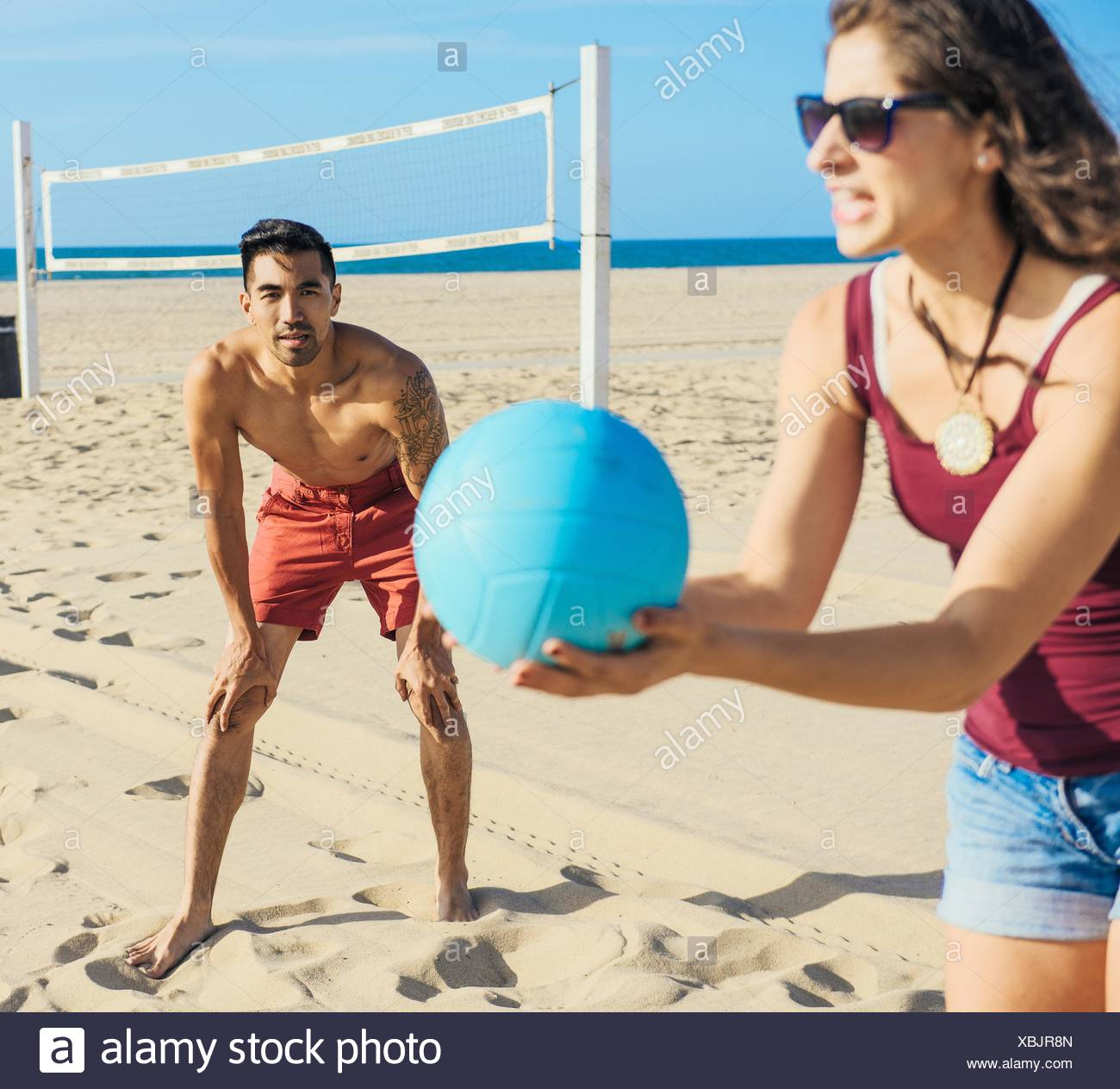 Groupe d'amis jouer au volley-ball sur plage Photo Stock