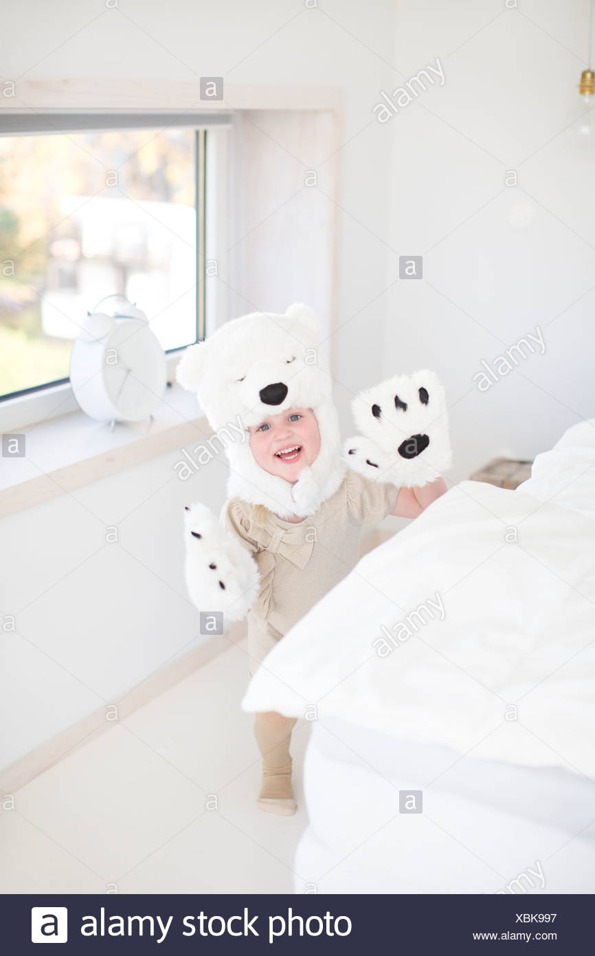 Girl costume d'ours polaires se cacher derrière bed Photo Stock