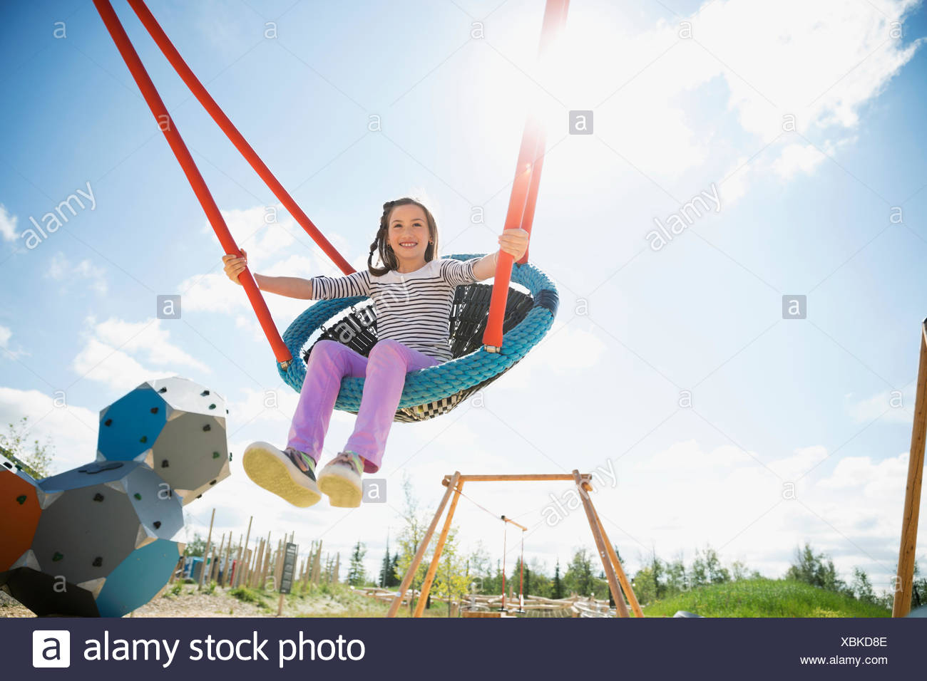 Carefree girl swinging à aire ensoleillée Photo Stock