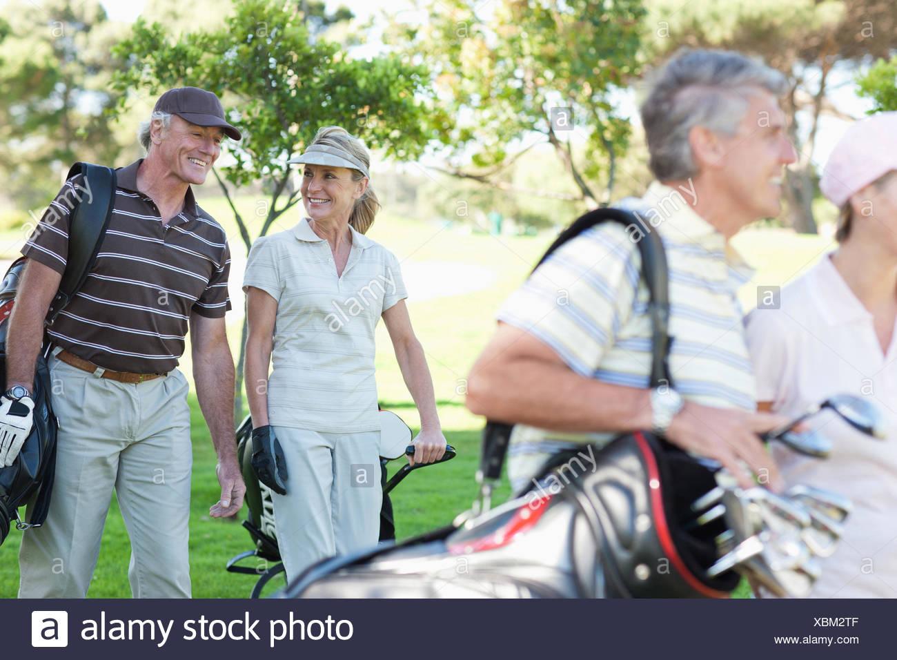 D'âge mûr portant des sacs de golf Photo Stock