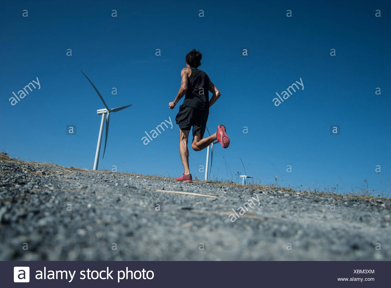 Mid adult man jogging jusqu'à une colline vers les éoliennes Photo Stock