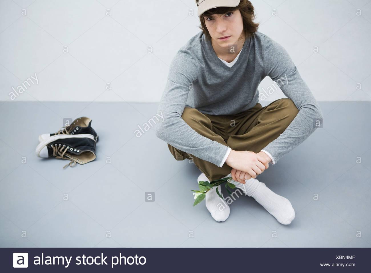 Jeune homme assis sur le sol à côté de ses chaussures, holding flower,  looking at camera db533502e30e