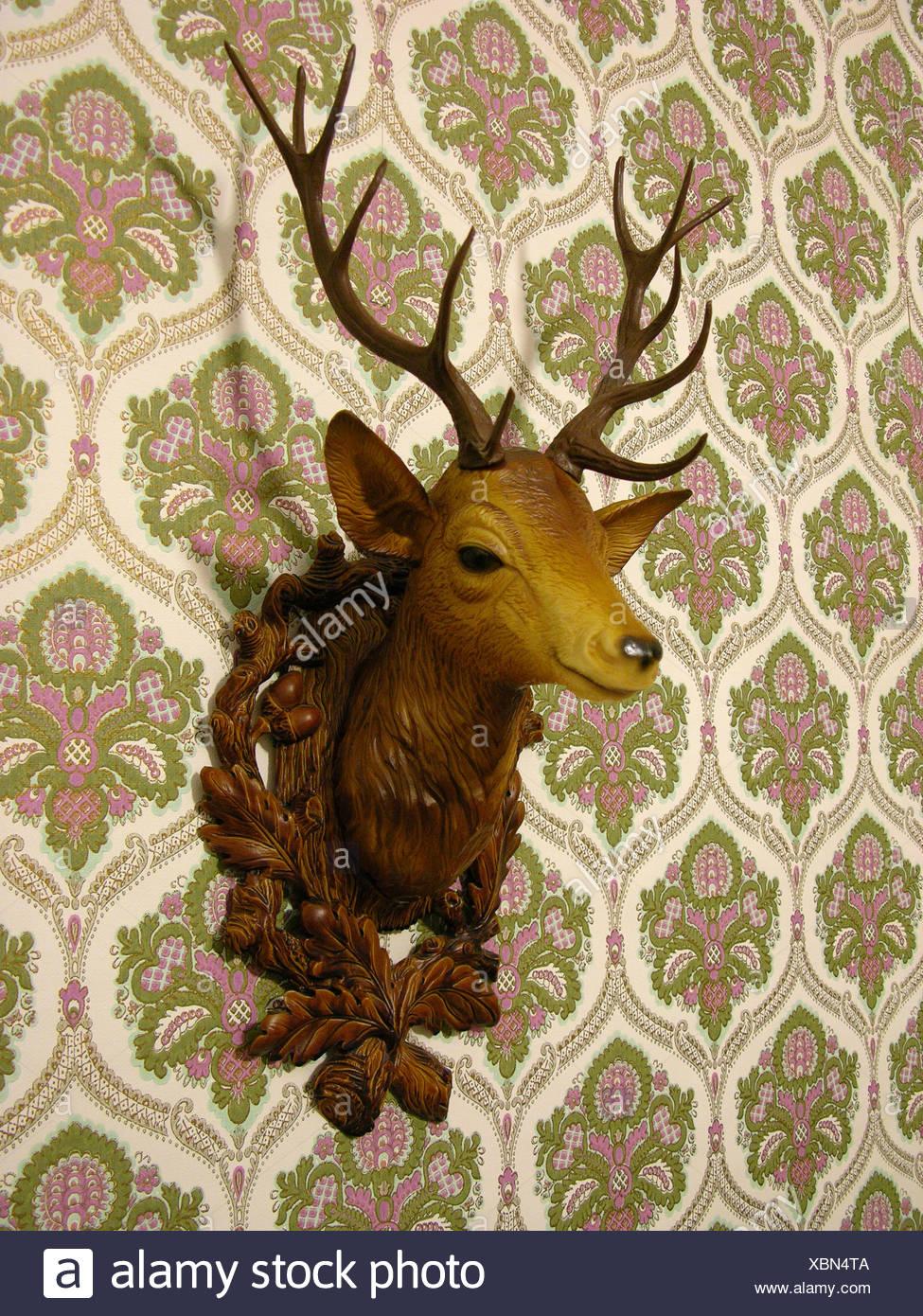 Tête de cerf en plastique sur un vieux papier peint Photo Stock