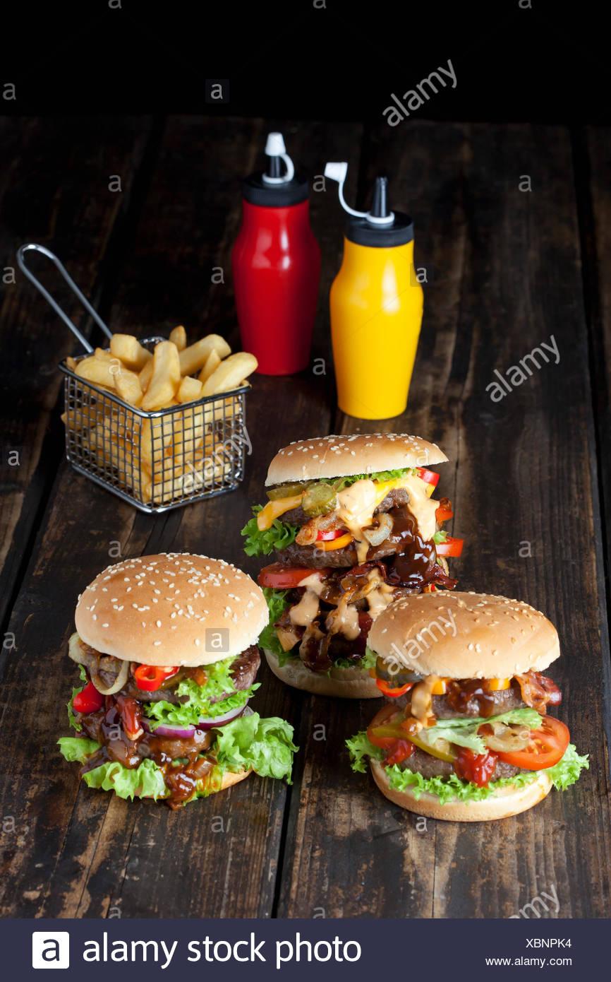 Grand hamburger accompagné de frites et de ketchup et moutarde en bouteilles Photo Stock