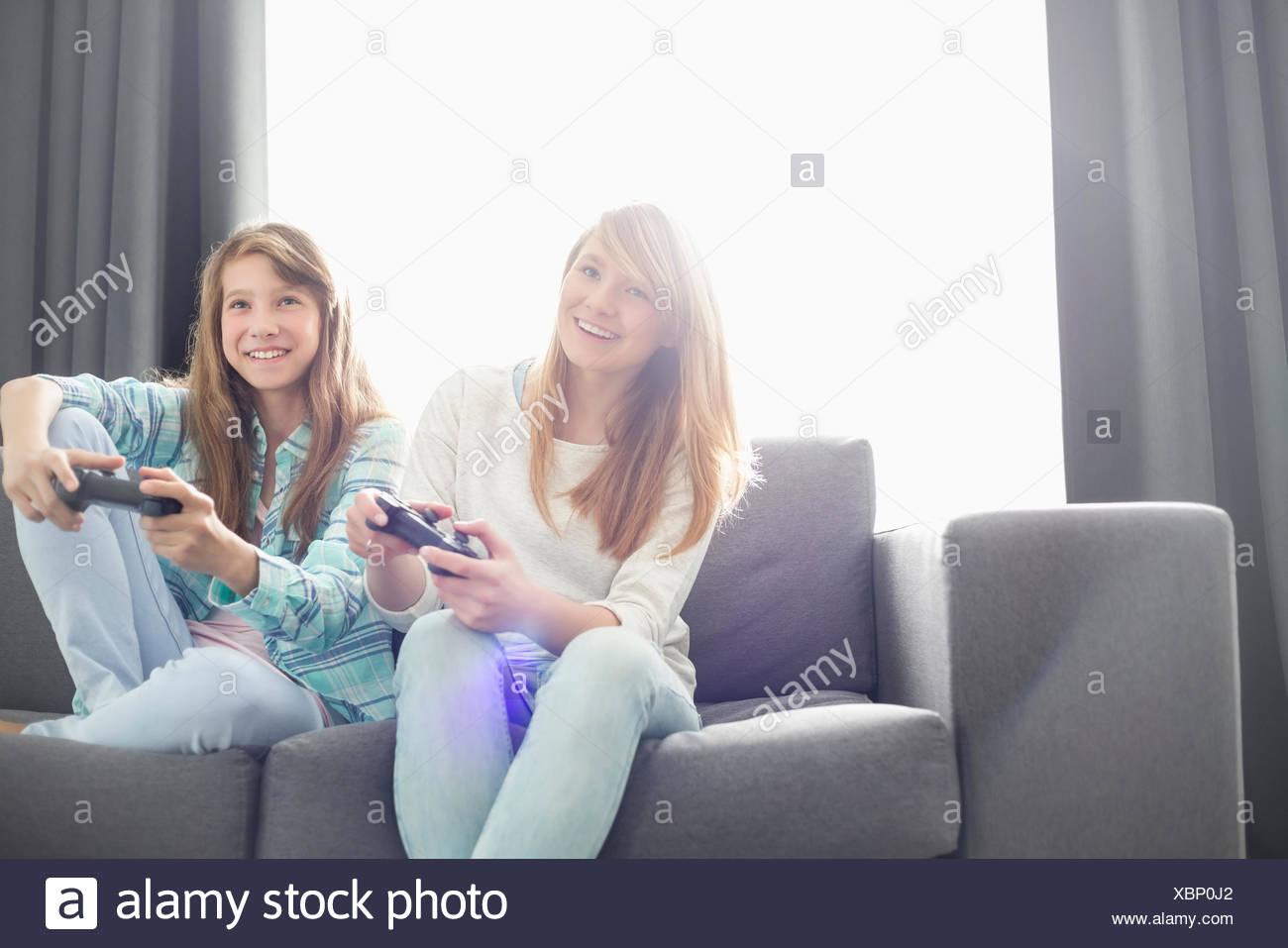 Soeurs à jouer aux jeux vidéo sur canapé Photo Stock