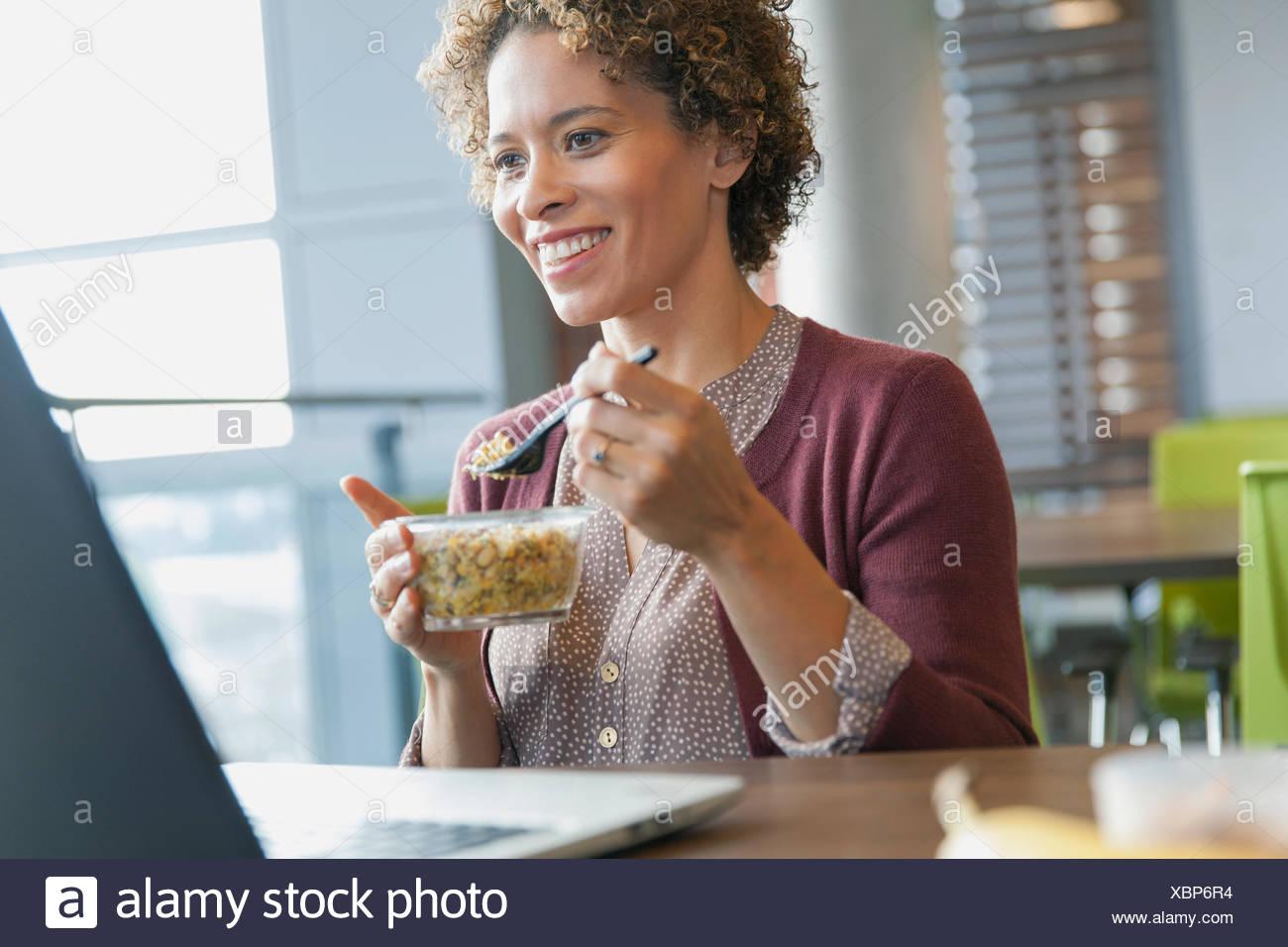 Femme sourire comme elle en-cas à son ordinateur portable. Photo Stock