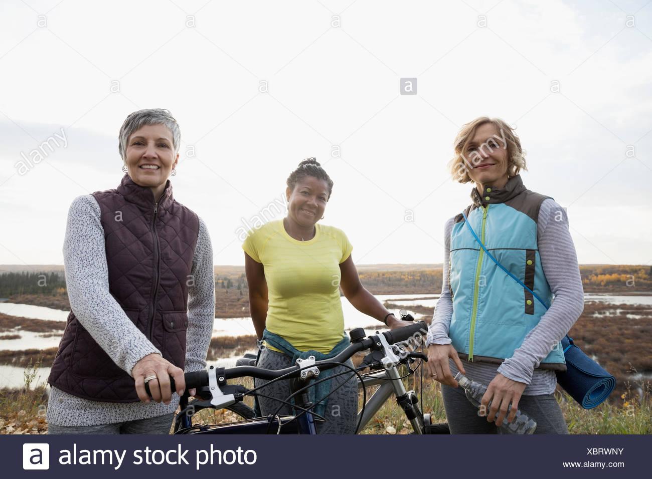 Portrait de femmes avec des amis de confiance des vélos sur colline Photo Stock