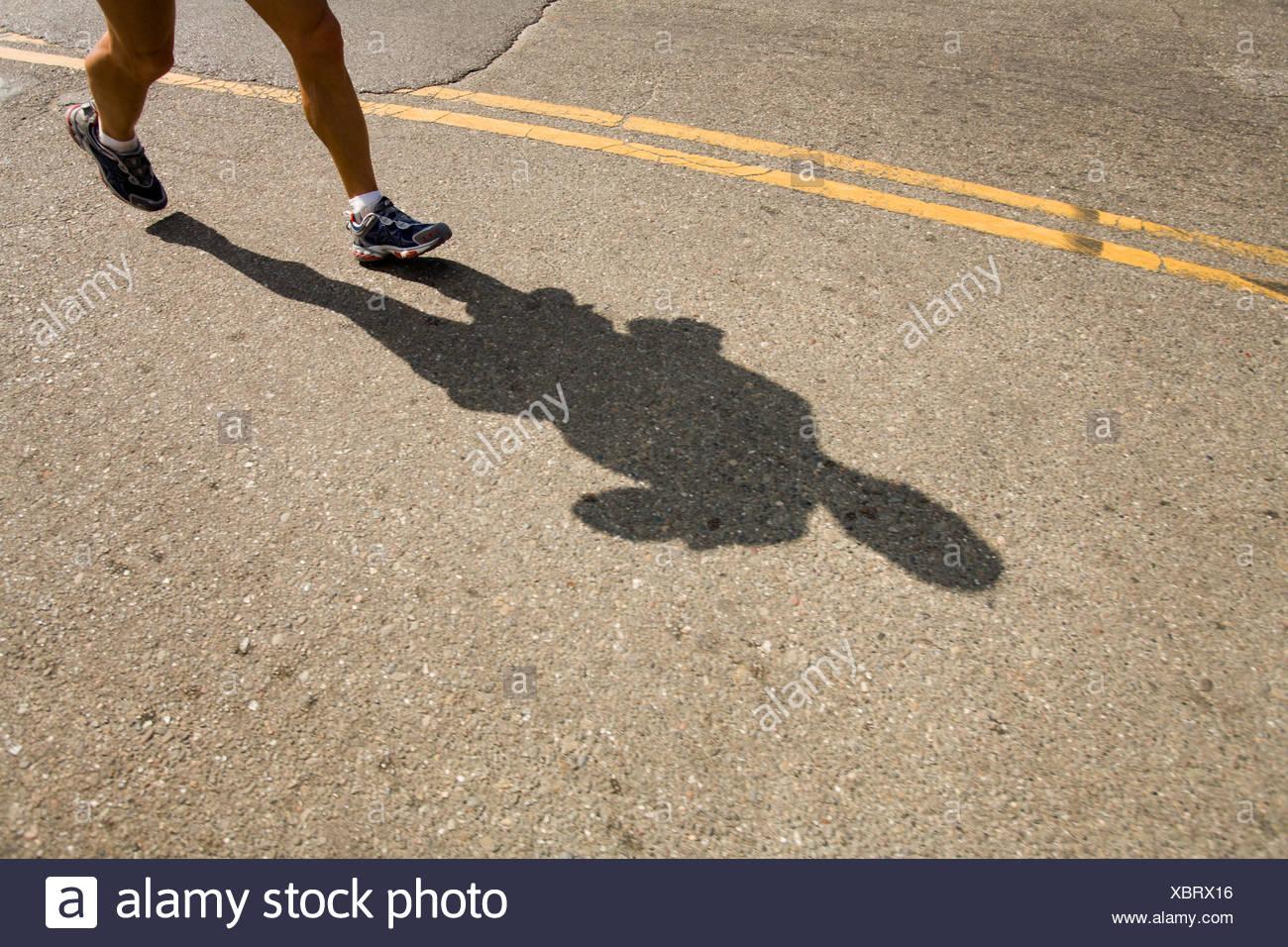 Ombre et les pieds d'un coureur au marathon de San Francisco, en Californie. Photo Stock