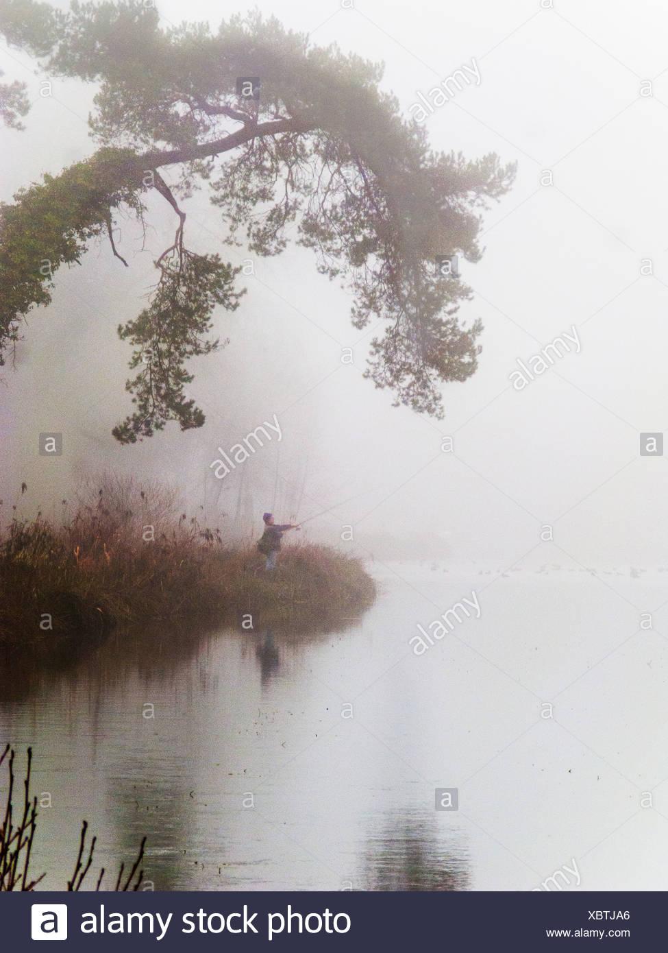 La pêche sur les rives de brouillard personne Photo Stock