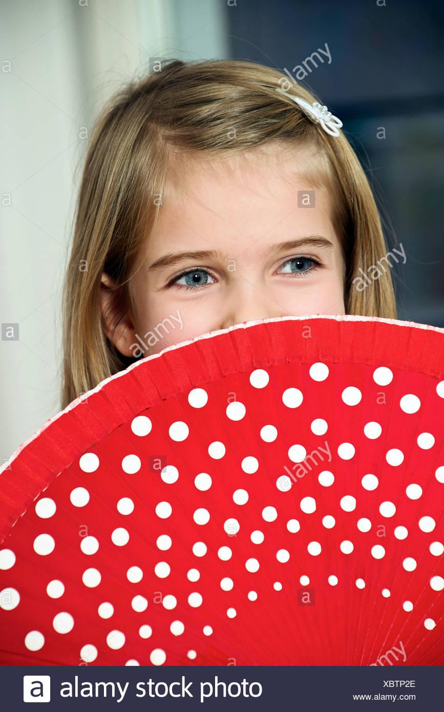 Girl holding red ventilateur avec points blancs Photo Stock