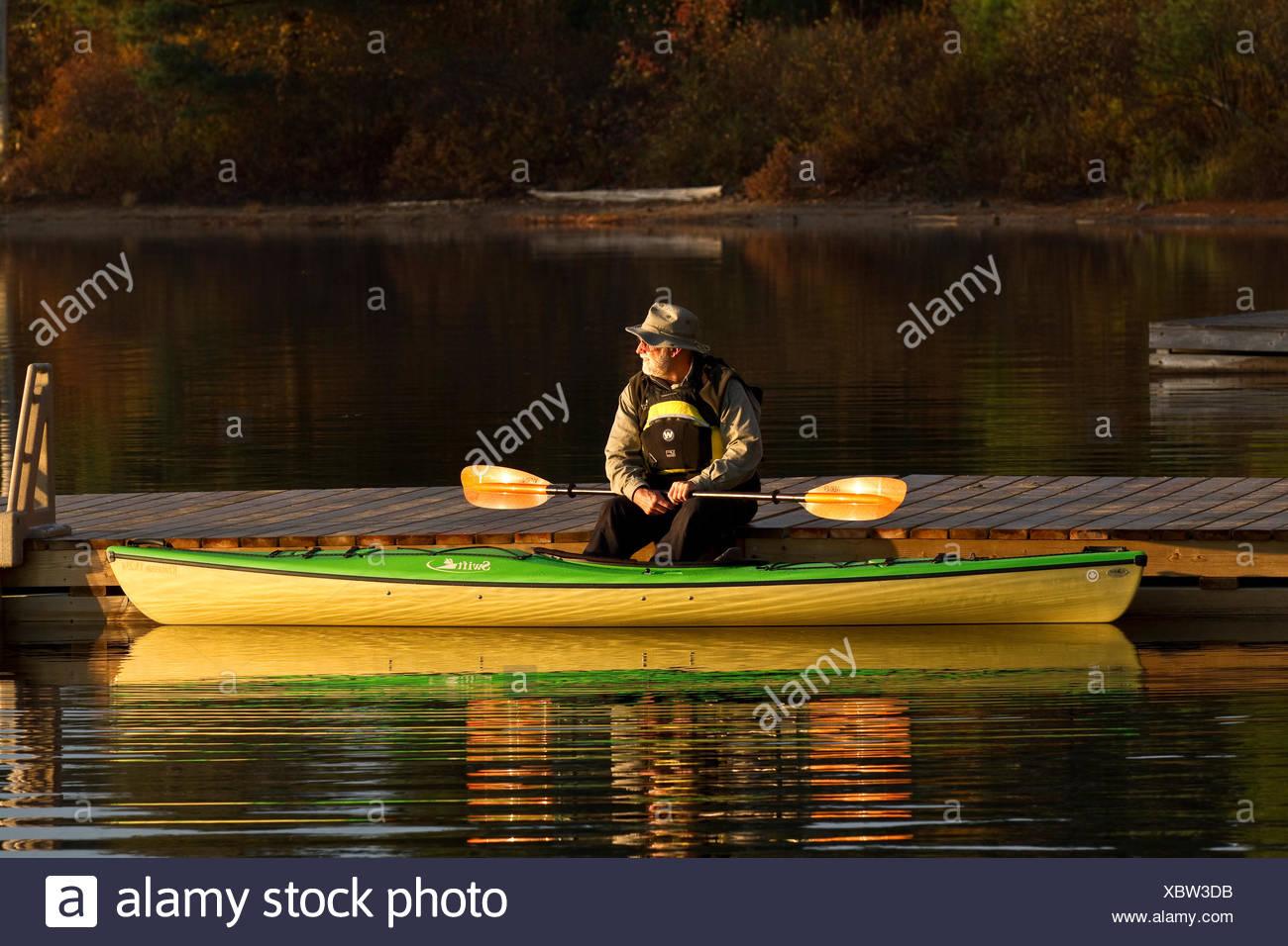 Homme âgé bénéficie d'matin calme sur un quai avec kayak sur le lac Oxtongue, Muskoka, Ontario, Canada. Photo Stock