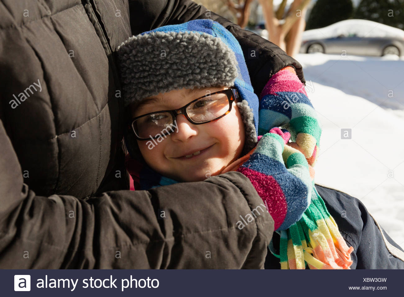 Mother hugging son wearing winter hat and glasses Photo Stock