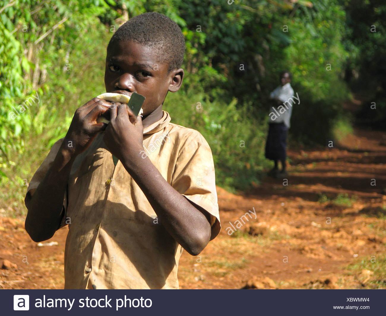 Garçon en zone rurale est de sucer sur une orange, l'homme regarde en arrière-plan, Haïti, Grande Anse, Jeremie Photo Stock