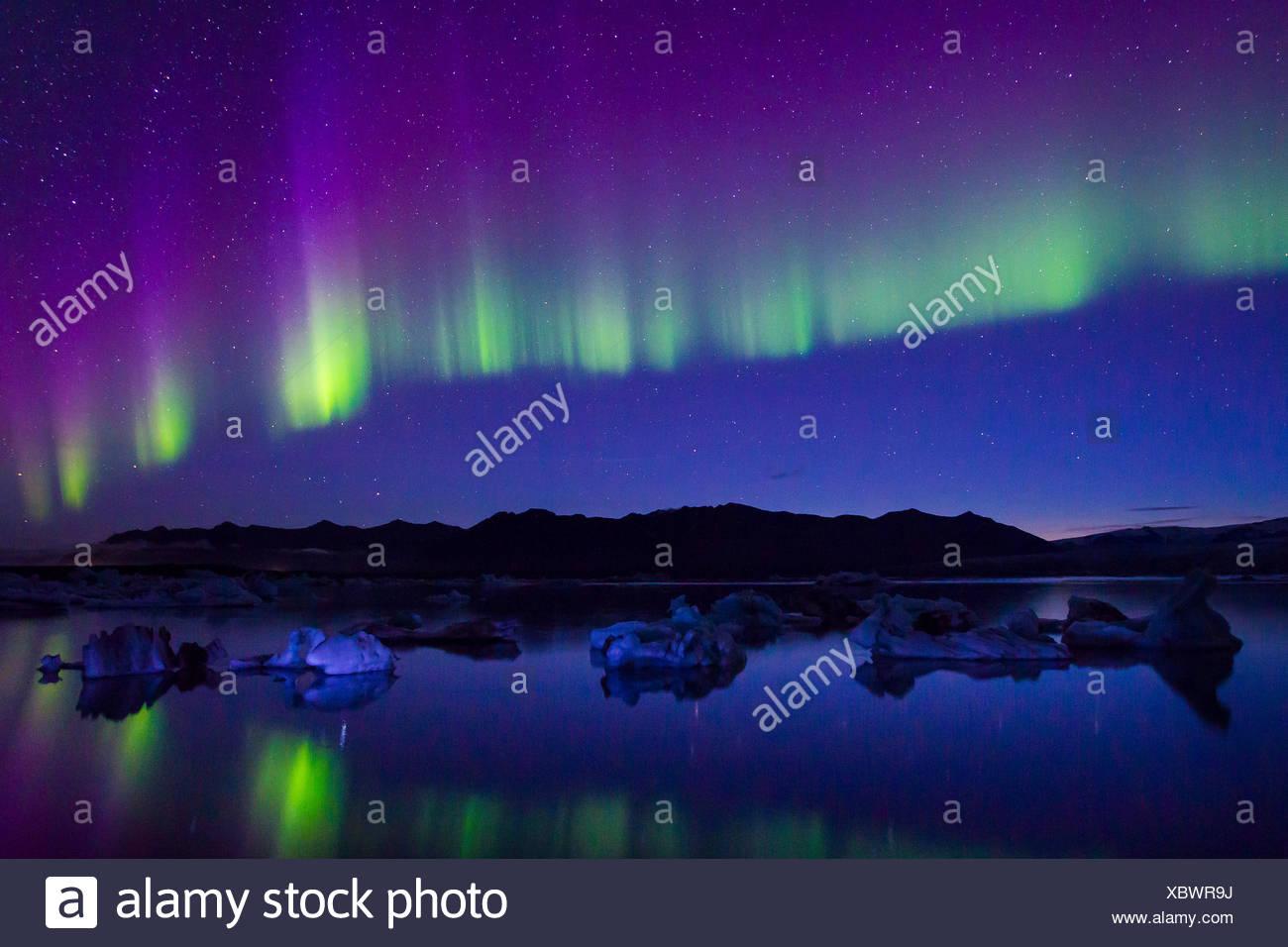 Northern Lights au cours d'une tempête solaire géomagnétique si intense qu'ils reflétaient l'eau glacée. Banque D'Images