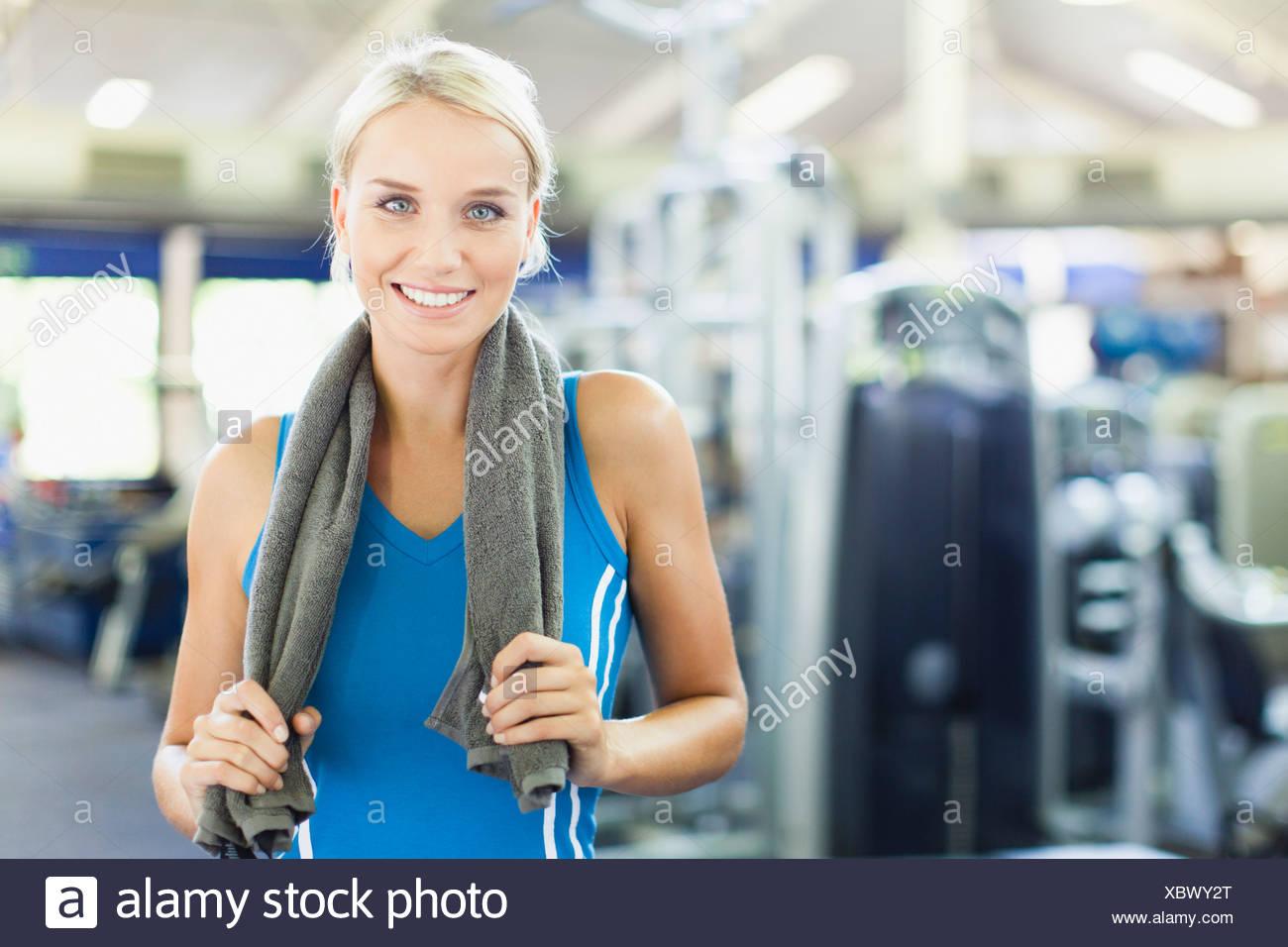 Femme tenant une serviette autour du cou en salle de sport Photo Stock