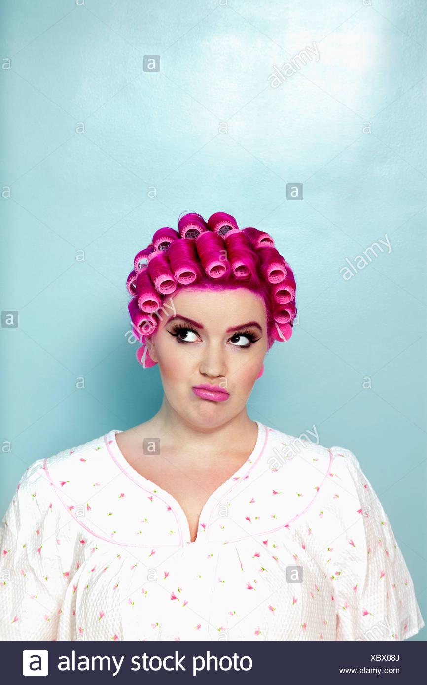 Jeune femme avec des bigoudis sur cheveux roses sur fond coloré Photo Stock