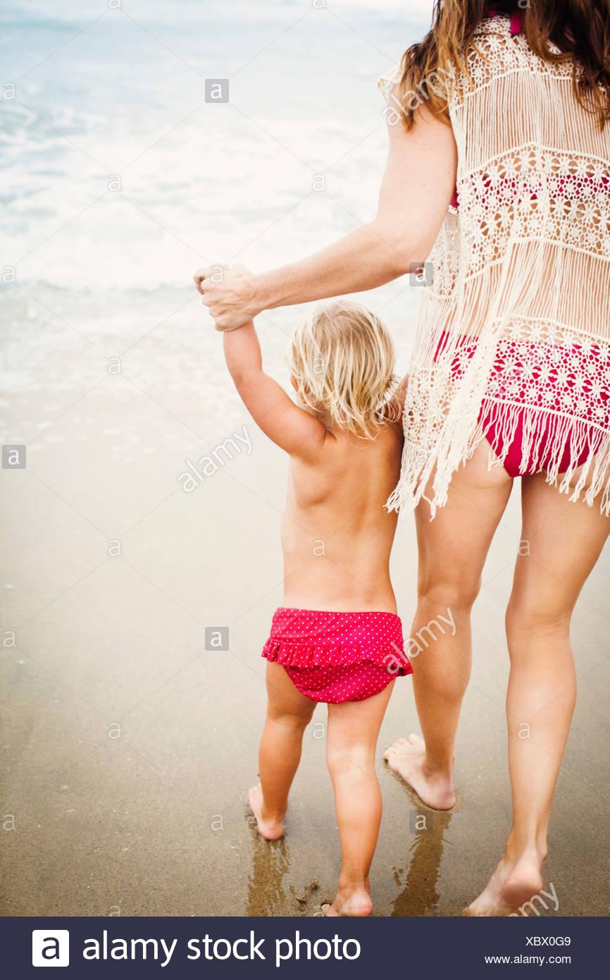 Vue arrière de l'enfant mère menant sur la plage Photo Stock