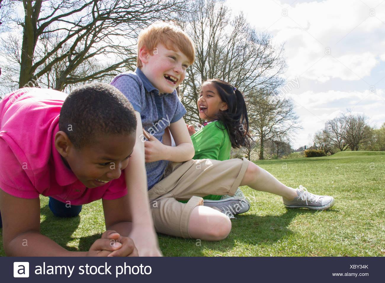 Deux garçons et une fille jouant dans le champ Banque D'Images