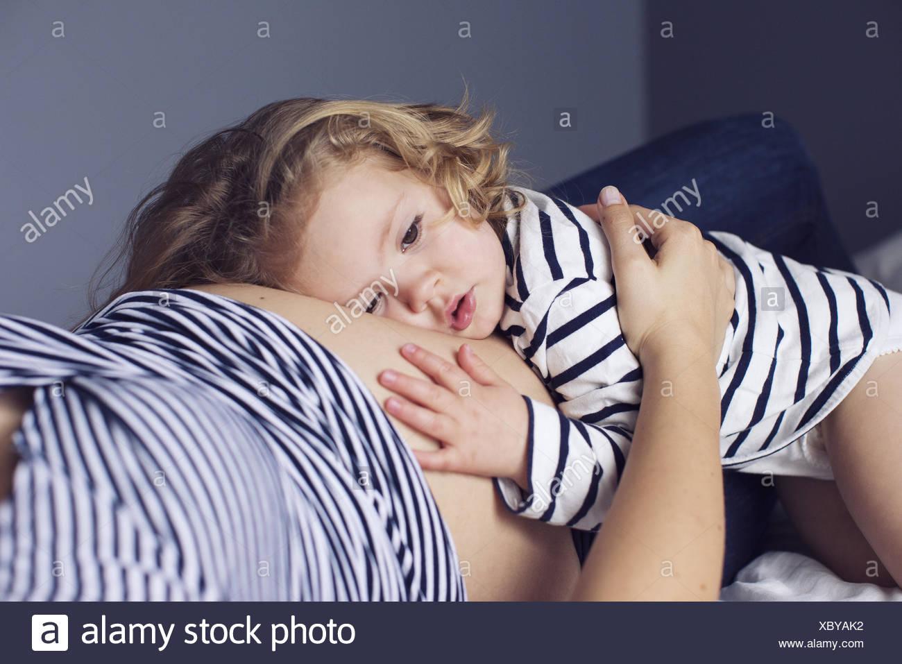 Petite fille posant sa tête et la main sur le ventre de la mère enceinte Photo Stock