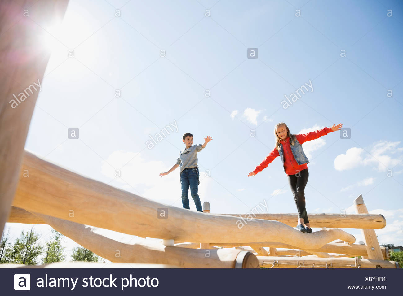 Boy and girl balancing sciage aire ensoleillée Photo Stock