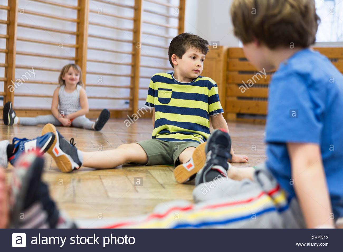 Des enfants assis sur le plancher en bois, les jambes Photo Stock