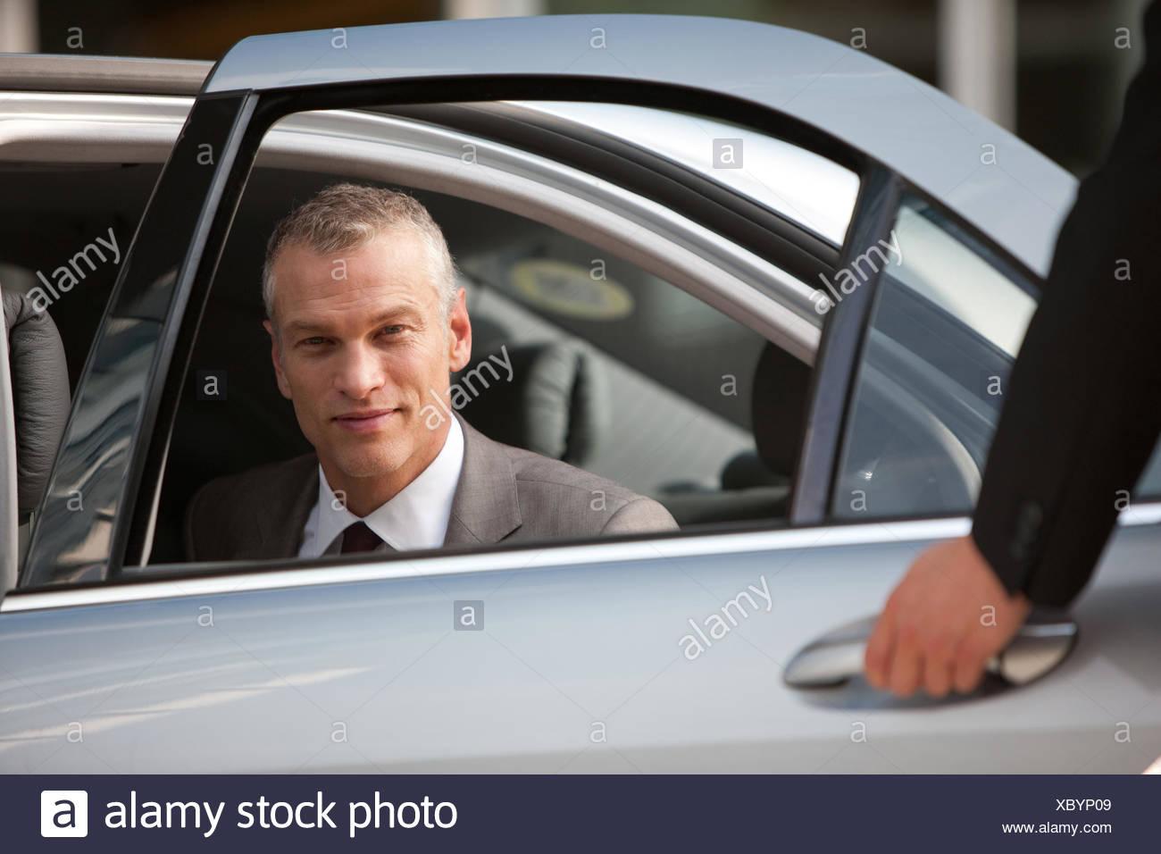Ouverture de porte de voiture avec chauffeur pour l'homme d'affaires Photo Stock