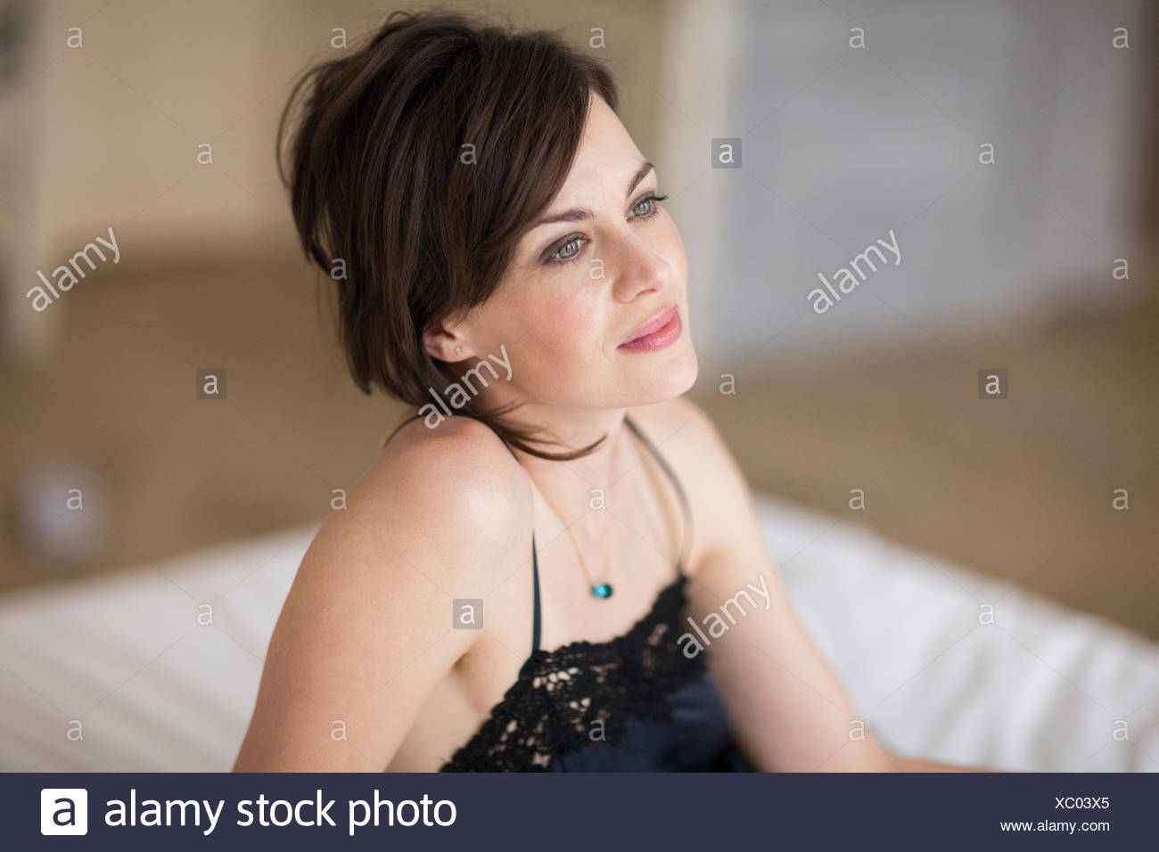 Belle femme assise sur le lit Photo Stock