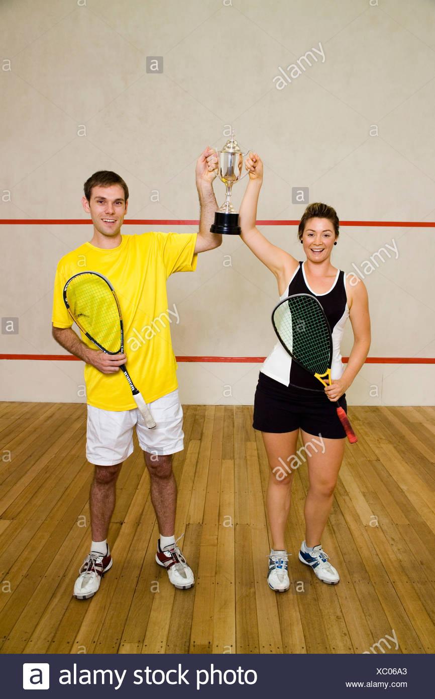 Deux autres membres de l'équipe de squash tient un trophée Photo Stock