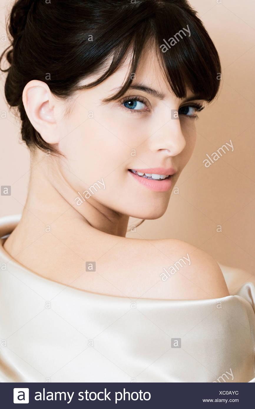 Portrait de jeune femme élégante dans une robe de soie blanche ou envelopper Photo Stock