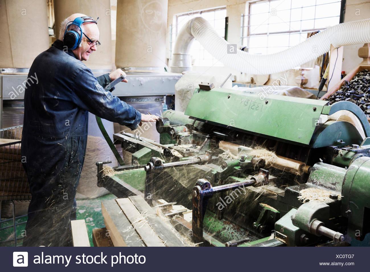 Homme debout dans un atelier de menuiserie, le port de protecteurs auditifs, travaillant à un tour à bois. Photo Stock