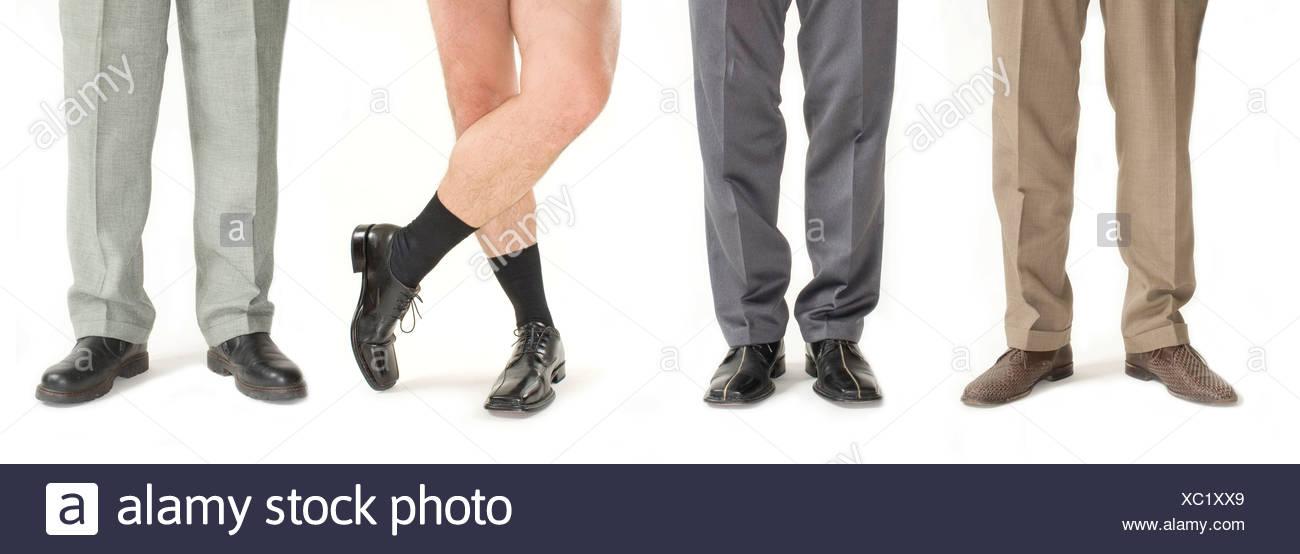Quatre businessmen standing dans une rangée, un pantalon sans détail, de jambes Photo Stock