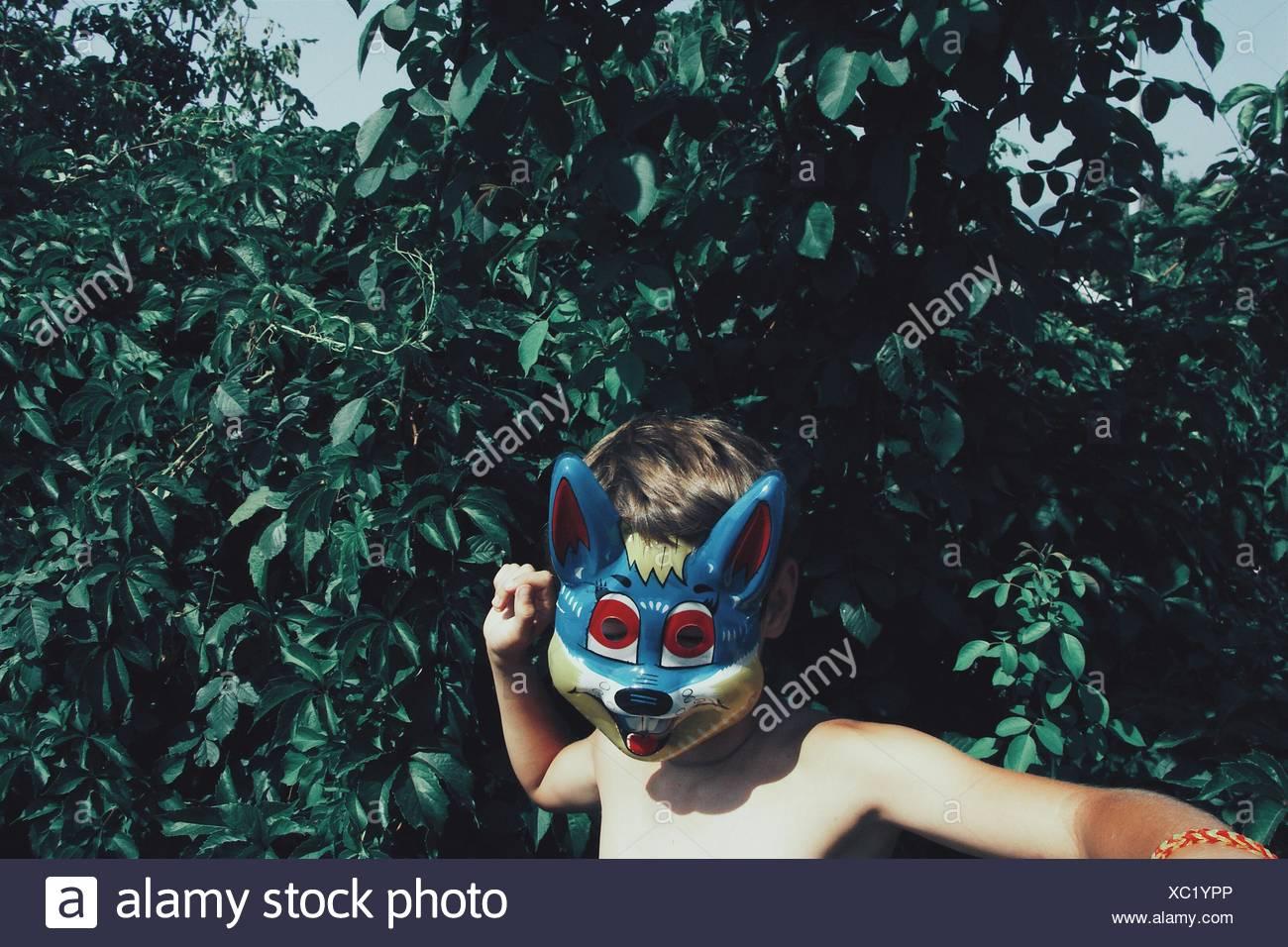 Shirtless Boy Wearing masque de renard à l'arrière-cour Photo Stock