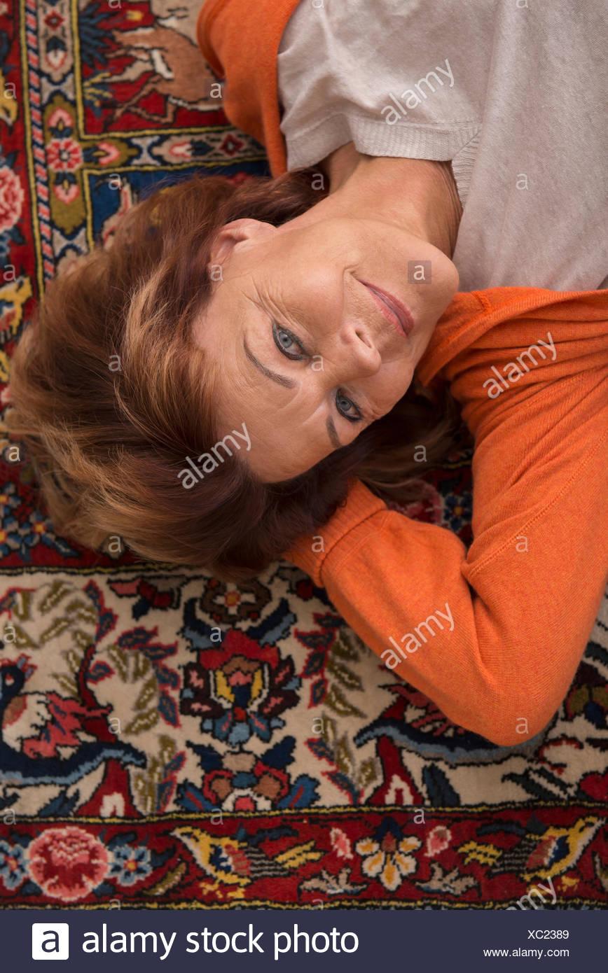 Portrait de senior woman lying on floor, Munich, Bavière, Allemagne Banque D'Images
