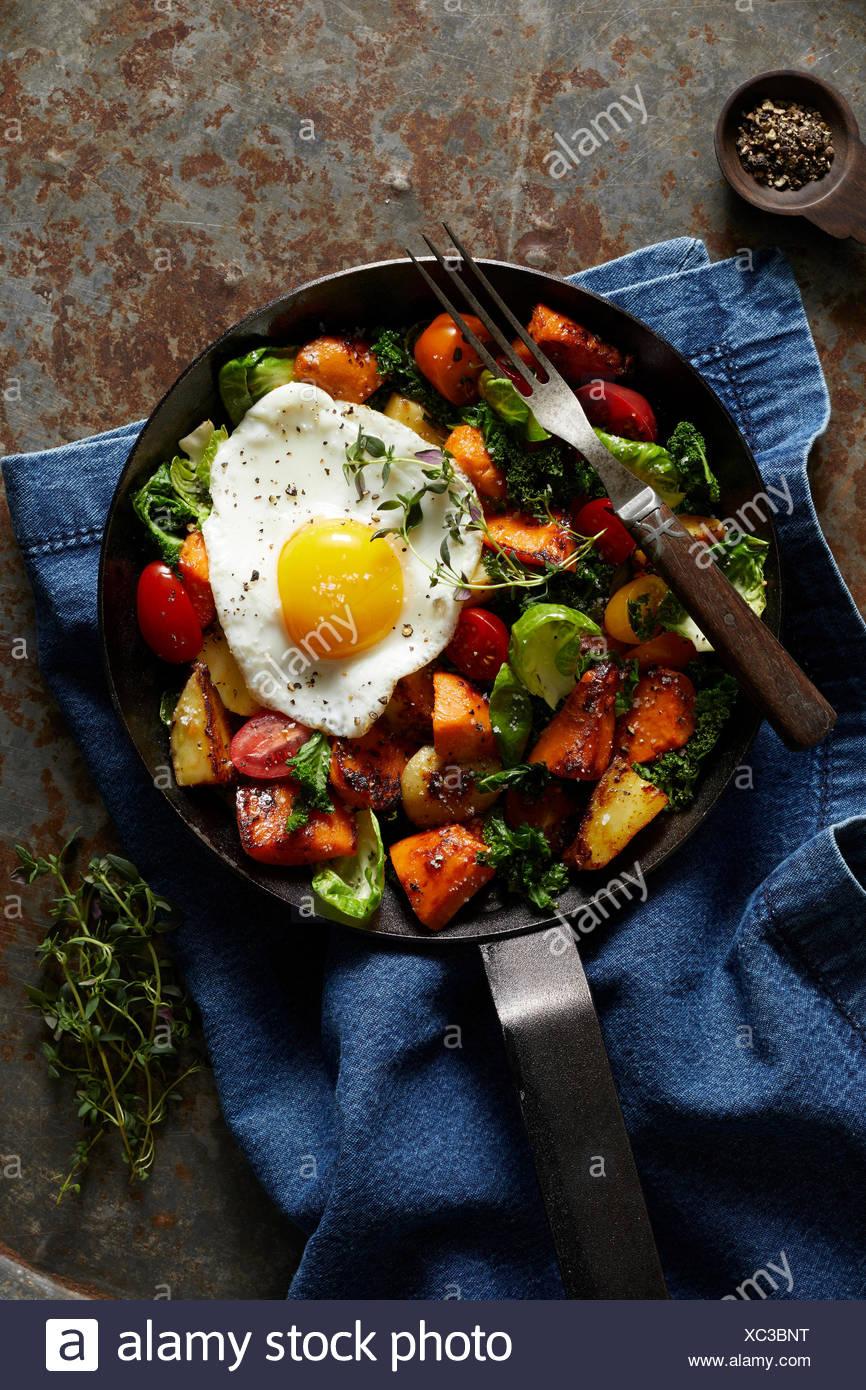 Petit-déjeuner de hachage avec œuf frit dans la poêle en fonte Photo Stock