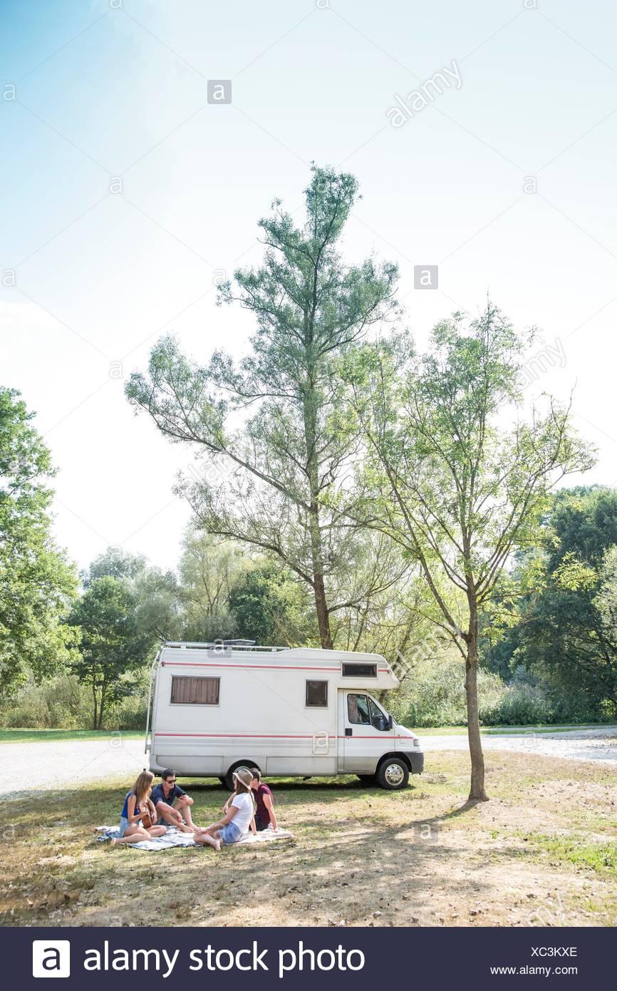 Groupe de jeunes adultes assis sur couverture de pique-nique , la détente, le camping-car en arrière-plan Photo Stock